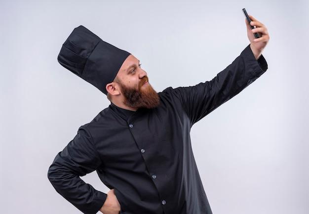 Een tevreden bebaarde chef-kok man in zwart uniform selfie met mobiele telefoon op een witte muur