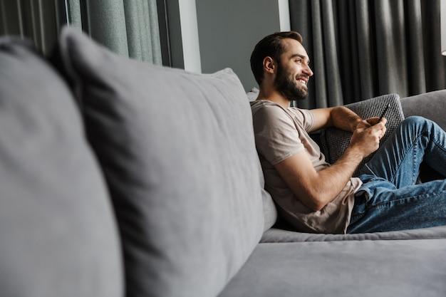 Een tevreden gelukkige jonge man binnenshuis thuis op de bank met behulp van mobiele telefoon.