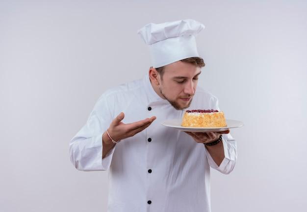 Een tevreden jonge, bebaarde chef-kok met een wit fornuisuniform en een hoed die een bord met cake vasthoudt en eraan ruikt terwijl hij op een witte muur staat