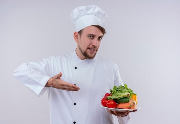 Een tevreden jonge bebaarde chef-kok met een wit fornuisuniform en hoed met een witte plaat met verse groenten zoals tomaten, komkommers, sla op een witte muur