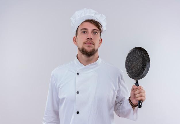Een tevreden jonge, bebaarde chef-kokmens die een wit fornuisuniform draagt en een hoed die zwarte koekenpan toont terwijl hij op een witte muur kijkt