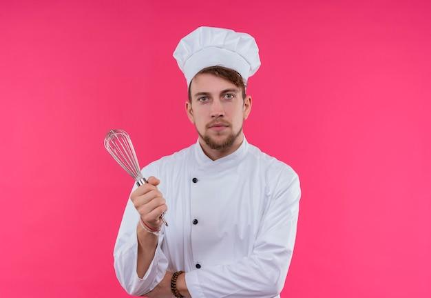 Een tevreden jonge, bebaarde chef-kokmens in wit uniform houdt mixerlepel vast terwijl hij op een roze muur kijkt