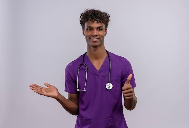 Een tevreden jonge knappe dokter met een donkere huid en krullend haar, gekleed in een violet uniform met een stethoscoop met omhoog duimen