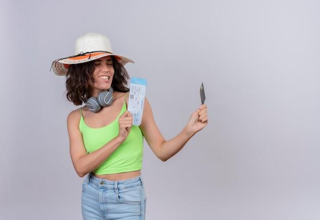 Een tevreden jonge vrouw met kort haar in een groene crop top in koptelefoon draagt een zonnehoed en kijkt naar vliegtickets en een creditcard op een witte achtergrond