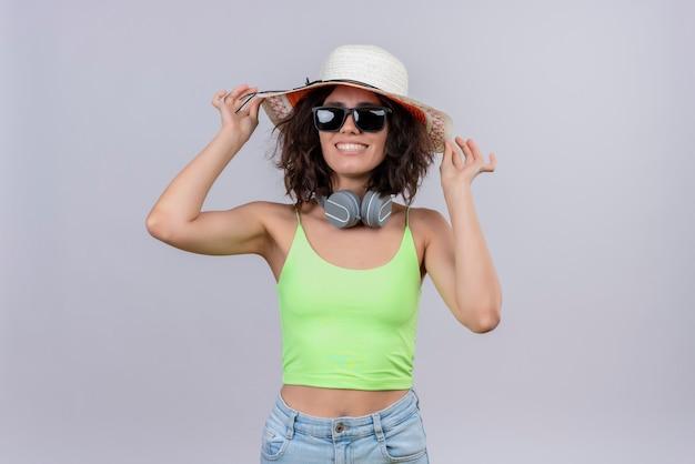 Een tevreden jonge vrouw met kort haar in een groene crop top met een zonnebril en zonnehoed op een witte achtergrond