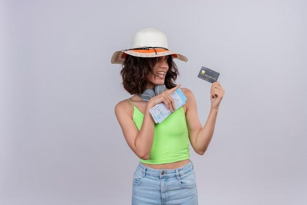 Een tevreden jonge vrouw met kort haar in groene crop top hoofdtelefoon dragen zonnehoed met vliegtickets wijzend op creditcard met wijsvinger op een witte achtergrond