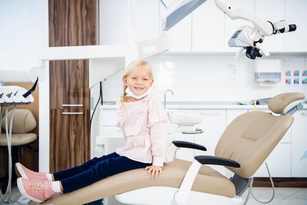 Een tevreden kleine tandartspatiënt die haar perfecte glimlach na behandeling in een kliniek toont