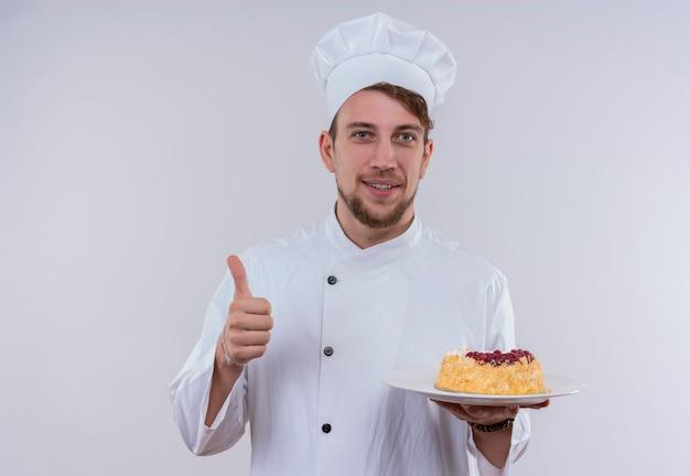 Een tevreden knappe jonge bebaarde chef-kok man in wit fornuis uniform en hoed met een bord met salade en duimen opdagen terwijl hij op een witte muur kijkt