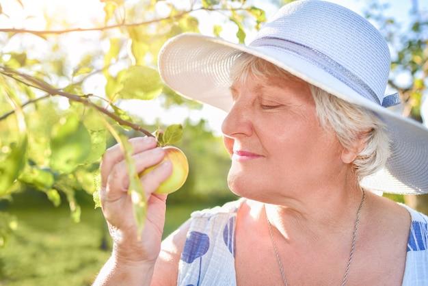 Een tevreden oudere vrouw geniet van de geur van een bloeiende appel die door haar tuin loopt