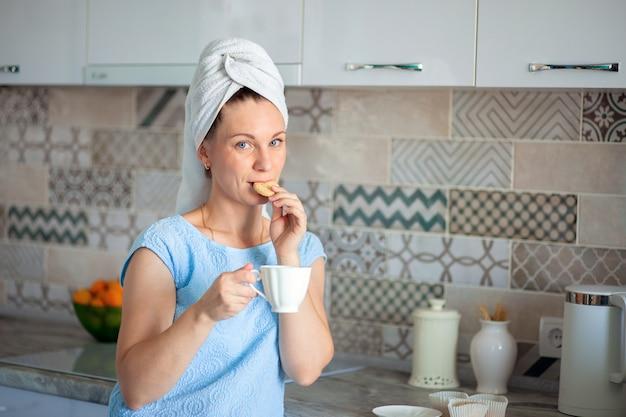 Een tevreden vrouw waste 's ochtends haar haren en drinkt met een handdoek over haar hoofd koffie en eet koekjes.
