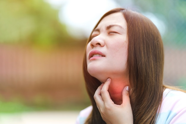 Een thaise vrouw legt haar hand op haar rode nek vanwege keelpijn of jeukende keel
