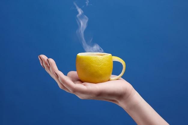 Een theekop gemaakt van citroen. citroenkop ter beschikking op een blauwe achtergrond. creatieve compositie op thema van natuurlijke fruitthee
