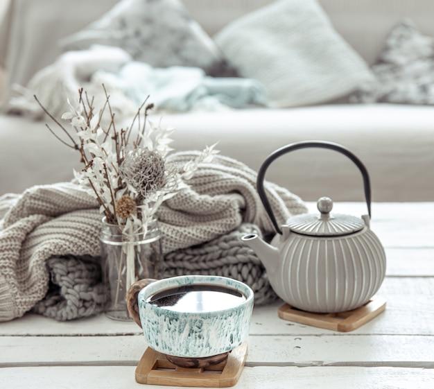 Een theepot en een mooie keramische beker met decordetails in een woonkamer in hygge-stijl
