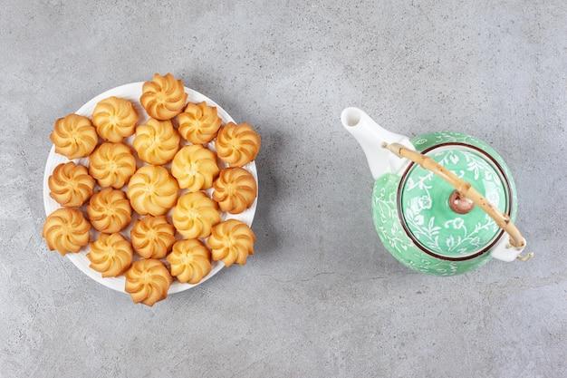 Een theepot en een schotel met zelfgemaakte koekjes op marmeren oppervlak