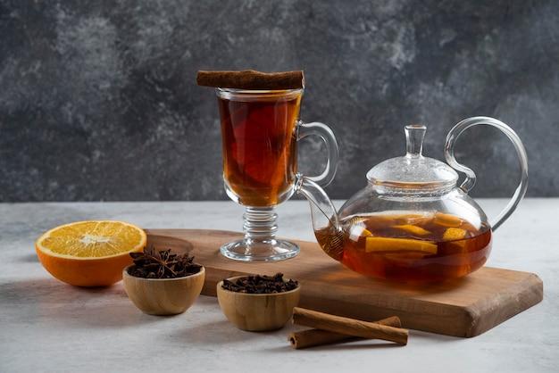 Een theepot met thee en een schijfje sinaasappel op een houten bord.