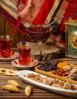 Een theeservies voor twee personen met een selectie snoepjes, confitures en droog fruit