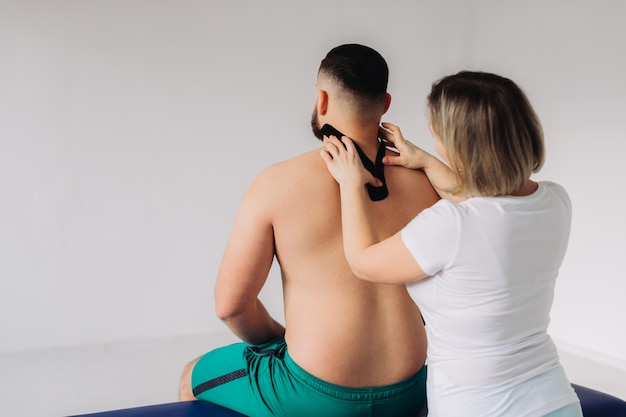 Een therapeut die kinesiologietape op patiëntenhals vastbindt.