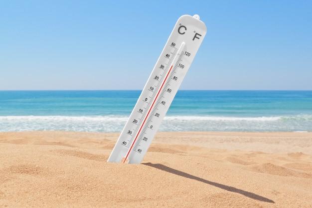 Een thermometer op het strand bij de zee om de temperatuur te controleren.