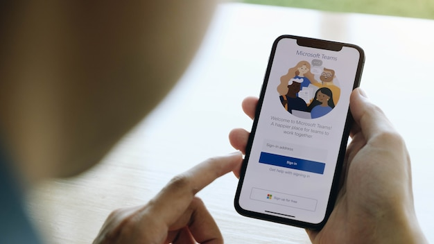 Een thuiswerkende medewerker downloadt het sociale platform microsoft teams, klaar om op afstand te werken in afzondering van huis