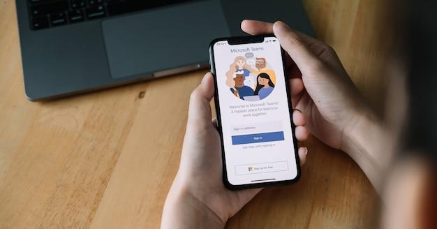 Een thuiswerkende medewerker downloadt het sociale platform van microsoft teams, klaar om op afstand te werken, geïsoleerd van thuis