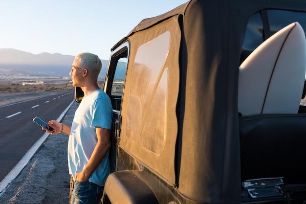 Een tiener alleen op straat met zijn auto bij zonsondergang die zijn telefoon gebruikt en naar de zon kijkt in zijn vakanties buitenshuis concept en levensstijl