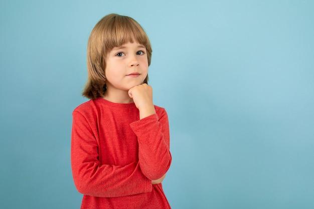 Een tiener blanke jongen in een rode jaket denkt, foto geïsoleerd op blauw