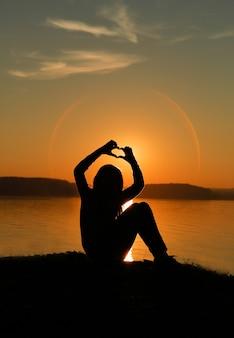 Een tiener die bij zonsondergang een hart maakt met je handen