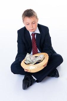 Een tiener die een hoed vasthoudt en bedelt.