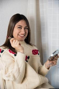 Een tiener die met een lippenstift en een spiegel glimlacht
