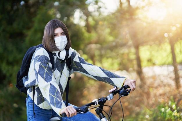 Een tiener die op de fiets naar school gaat en een gezichtsmasker draagt vanwege de pandemie van het coronavirus