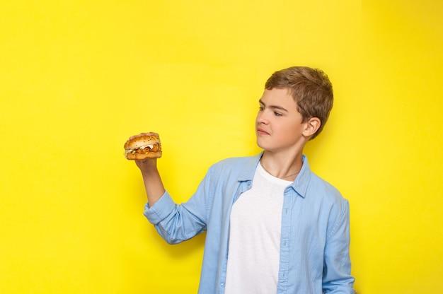 Een tiener heeft een hamburger in zijn hand