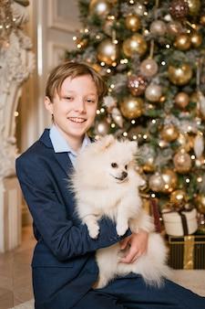 Een tiener houdt witte spitz in zijn armen in blauwe jas tegen de achtergrond van de kerstboom en lacht...