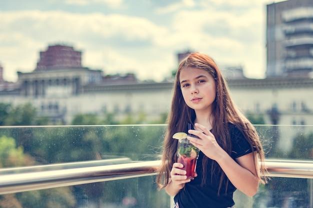 Een tiener in een café drinkt een koud drankje op een warme dag. meisje in een zwart t-shirt. tiener