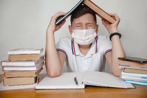 Een tiener in een masker die thuis bij lessen zit, bedekt zijn hoofd met schoolboeken. coronavirus concept