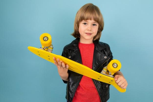 Een tiener kaukasische jongen houdt een gele cent in handen, foto geïsoleerd op blauwe achtergrond