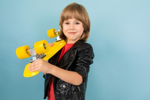 Een tiener kaukasische jongen houdt een gele stuiver in handen en glimlacht, foto geïsoleerd op blauw