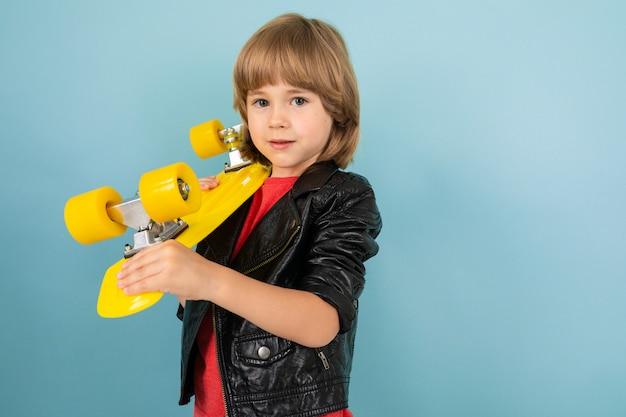 Een tiener kaukasische jongen houdt een gele stuiver in handen, foto geïsoleerd op blauw oppervlak