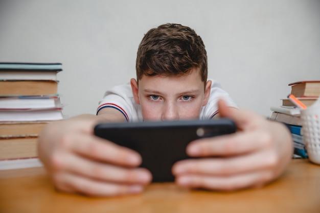 Een tiener kijkt naar een zwarte smartphone terwijl hij hem op armlengte thuis aan een tafel tussen schoolboeken vasthoudt