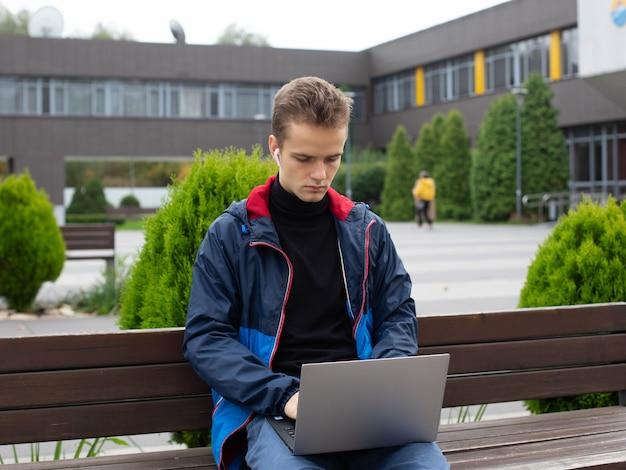 Een tiener met een koptelefoon, een student zit op een bankje met een laptop in een park vlakbij de universiteit
