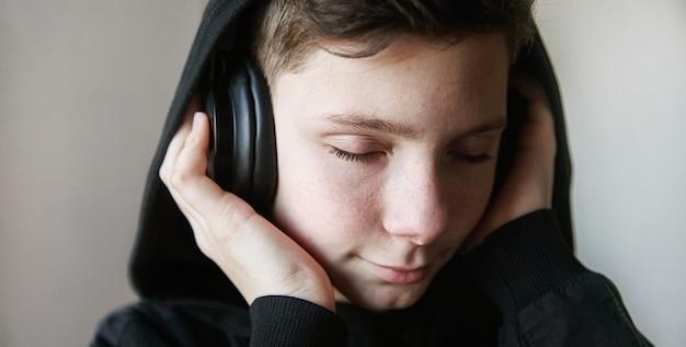 Een tiener met een zwarte kap en een grote koptelefoon luistert naar muziek met zijn ogen dicht