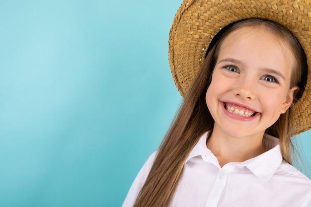 Een tiener met grijze ogen, mooie glimlach en met hoed glimlachen geïsoleerd op blauw