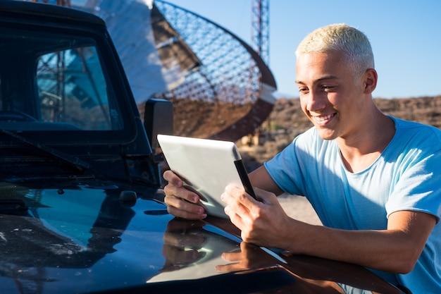Een tiener of blanke man die zijn tablet en apparaat alleen op zijn autovoertuig gebruikt - technologieverslaafd concept en online levensstijl - reiziger in vakanties die naar de kaarten op zijn tablet kijkt
