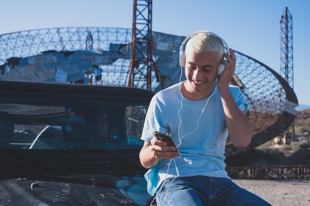 Een tiener of blanke man die zijn telefoon en apparaat alleen in zijn auto gebruikt - technologieverslaafd concept en online levensstijl - reiziger in vakanties die naar de kaarten op zijn tablet kijkt