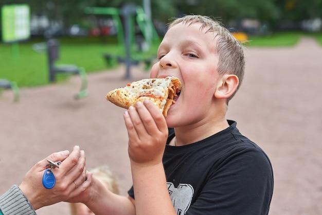 Een tiener op straat eet een stuk pizza en geeft de sleutel van hand tot hand
