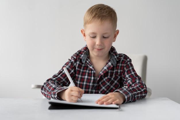 Een tiener studeert op afstand. de jongen schrijft een taak in een notitieblok met een pen