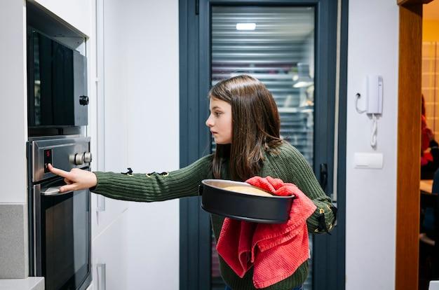 Een tiener zet een taart in de oven
