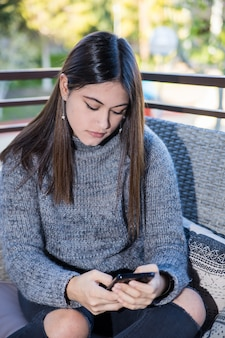 Een tiener zit op een terras en kijkt naar haar mobiele telefoon
