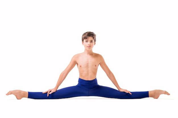 Een tienerballetdanseres poseert in blauwe nauwsluitende panty, blootsvoets, geïsoleerd tegen een witte achtergrond.