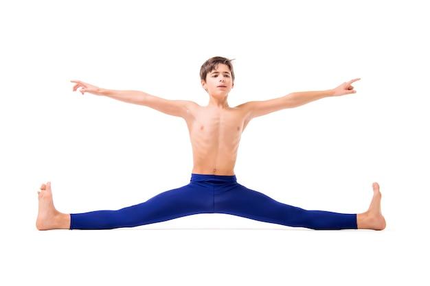 Een tienerballetdanseres poseert in blauwe nauwsluitende panty's, blootsvoets, geïsoleerd tegen een witte achtergrond.