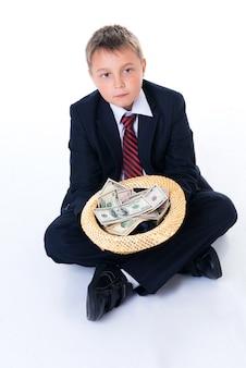 Een tienerjongen in schooluniform die een hoed vasthoudt en om geld smeekt.